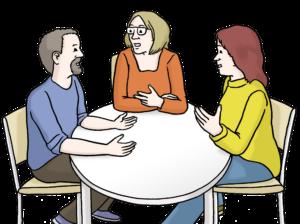 Bild zeigt drei Personen an einem Tisch, die besprechen.